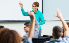 Professor smiling, students hands raised