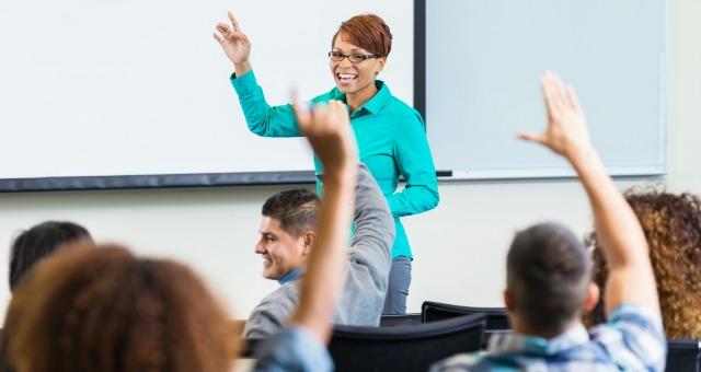 Professor smiling, students hands raised