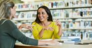Professors chatting in library.