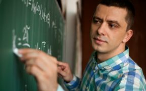 young professor at chalkboard