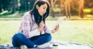 A student sitting cross-legged on a picnic blanket reads a letter on her smartphone