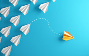 A yellow paper plane deviates from a formation of white paper planes