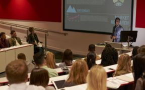 Wide shot of a university classroom in which a male professor lecture with PowerPoint slides